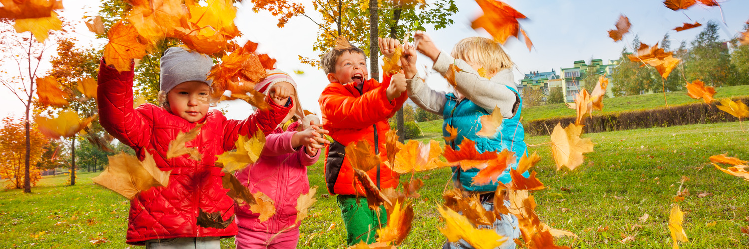 Active group of children playing with flying maple leaves and enjoying wonderful autumn day